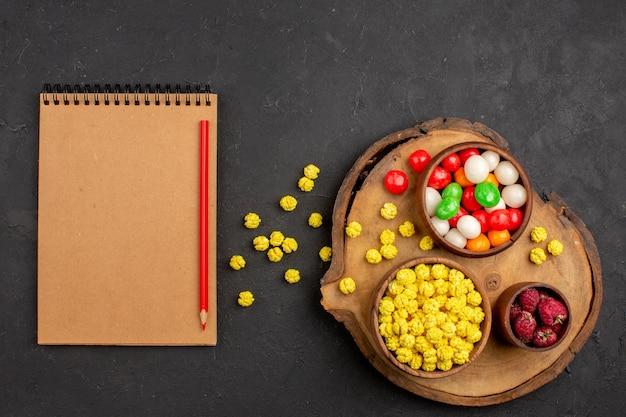 Bovenaanzicht kleurrijke snoepjes met notitieblok op donkere ruimte