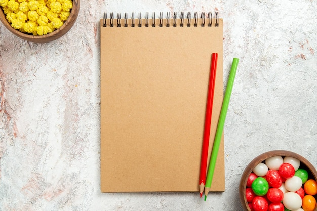 Bovenaanzicht kleurrijke snoepjes met notitieblok op wit bureau regenboogkleuren kandijsuiker