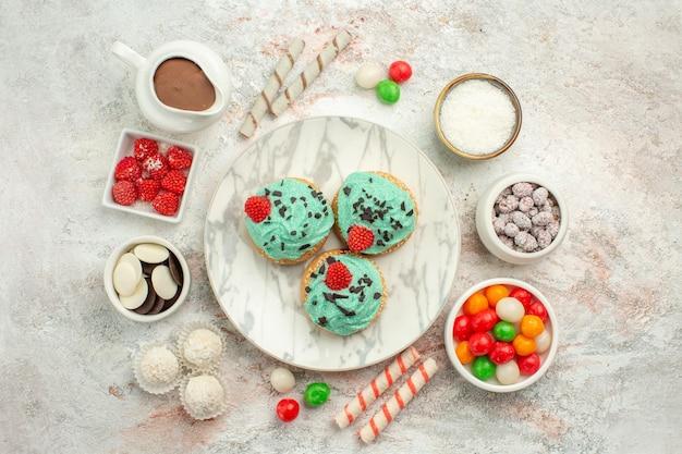 Bovenaanzicht kleurrijke snoepjes met slagroomtaarten op wit oppervlak biscuit zoete cake thee cookie