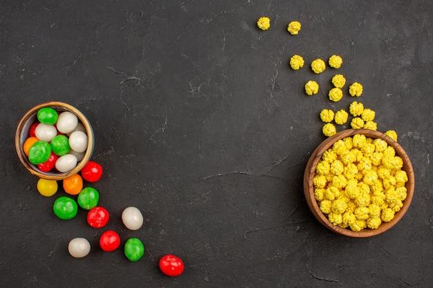 Bovenaanzicht kleurrijke snoepjes op donkere ruimte