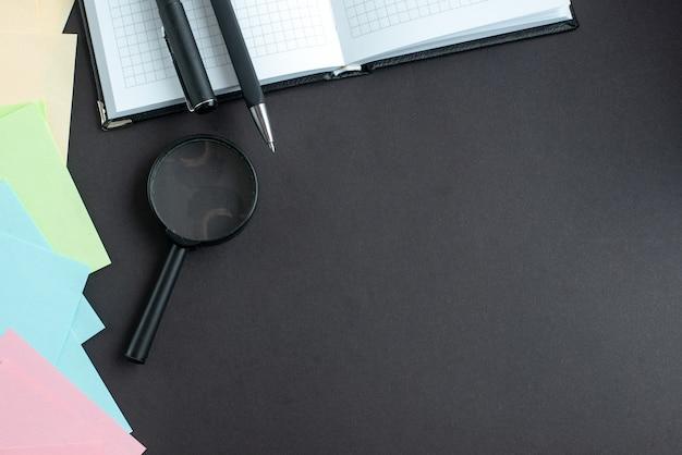 Bovenaanzicht kleurrijke stickers met pennen op donkere achtergrond