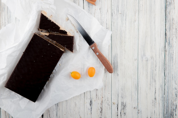 Bovenaanzicht knapperige wafel cake met kumquat en mes op witte houten achtergrond