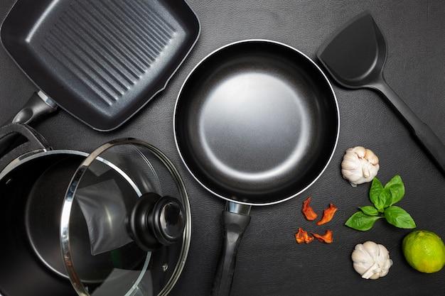 Bovenaanzicht koekenpan en pot op zwart lederen achtergrond