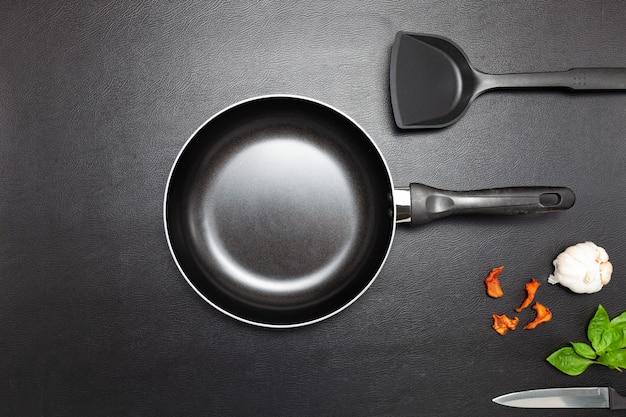 Bovenaanzicht koekenpan en pot op zwart lederen tafel achtergrond