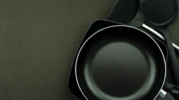 Bovenaanzicht koekenpan en pot op zwarte achtergrond.
