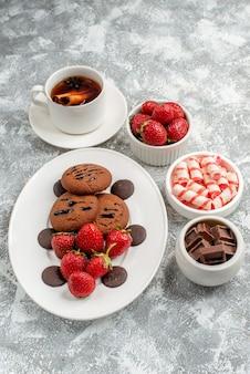 Bovenaanzicht koekjes aardbeien en ronde chocolaatjes op de ovale plaat kommen met snoepjes aardbeien chocolaatjes en kaneelthee op de grijs-witte tafel