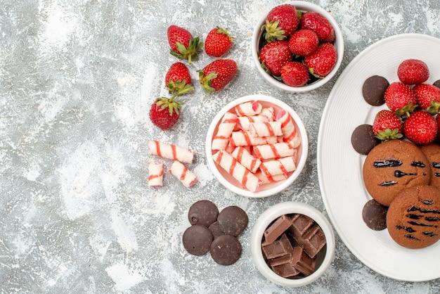 Bovenaanzicht koekjes aardbeien en ronde chocolaatjes op de ovale schaal schalen met snoep aardbeien chocolaatjes aan de rechterkant van de grijs-witte tafel
