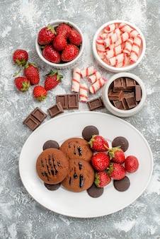 Bovenaanzicht koekjes aardbeien en ronde chocolaatjes op de witte ovale plaat en kommen met snoep aardbeien chocolaatjes op de grijs-witte tafel