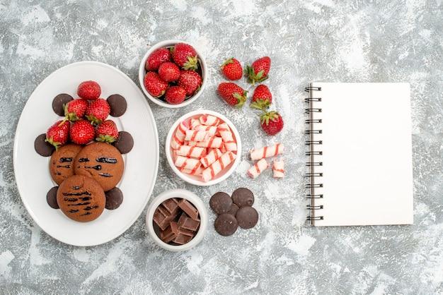 Bovenaanzicht koekjes aardbeien en ronde chocolaatjes op de witte ovale plaat kommen met snoepjes aardbeien chocolaatjes en notitieboekje op de grijs-witte tafel
