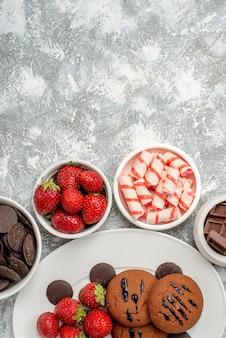 Bovenaanzicht koekjes aardbeien en ronde chocolaatjes op de witte ovale plaat omgeven kommen met snoep aardbeien en chocolaatjes onderaan de grijs-witte tafel