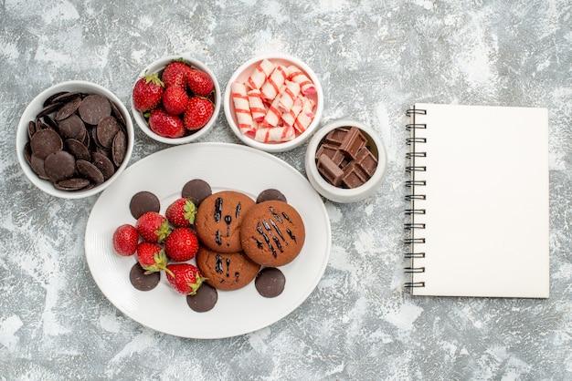 Bovenaanzicht koekjes aardbeien en ronde chocolaatjes op de witte ovale plaat omgeven kommen met snoepjes, aardbeien en chocolaatjes en een notitieboekje op de grijs-witte tafel