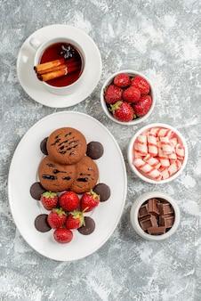 Bovenaanzicht koekjes aardbeien en ronde chocolaatjes op het ovale bord afgerond met kommen snoep aardbeien chocolaatjes kaneel thee op de grijs-witte tafel