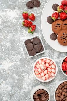 Bovenaanzicht koekjes aardbeien en ronde chocolaatjes op het ovale bord kommen met snoepjes aardbeien chocolaatjes granen aan de rechterkant van de grijs-witte tafel