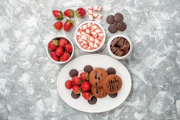 Bovenaanzicht koekjes aardbeien en ronde chocolaatjes op het witte ovale bord schalen met snoep aardbeien chocolaatjes in het midden van de grijs-witte tafel