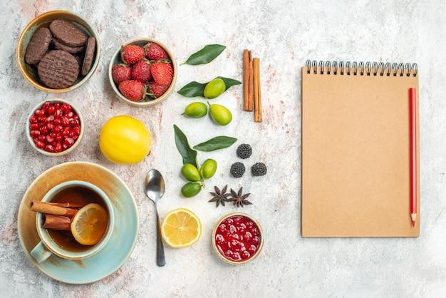 Bovenaanzicht koekjes en bessen crème notitieboekje en rood potlood naast de kaneel de smakelijke koekjes aardbeien citroen lepel een kopje thee citrusvruchten op tafel