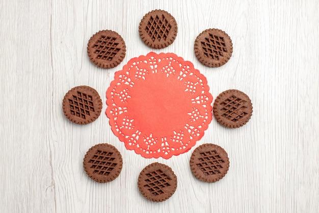 Bovenaanzicht koekjes en het rode ovale kanten kleedje op de witte houten tafel