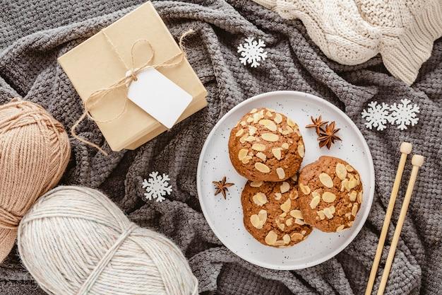 Bovenaanzicht koekjes, garen en geschenkdoos op deken