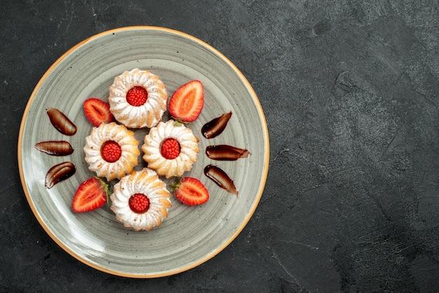 Bovenaanzicht koekjes met aardbeienkoekjes met chocolade en aardbei op witte plaat aan de linkerkant van de tafel