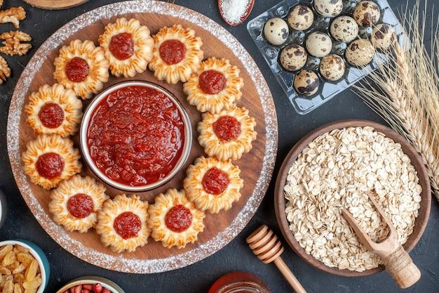 Bovenaanzicht koekjes met jam en jam kom op een houten bord haver in kom tarwe spikes kwarteleitjes in viol noten in kommen op donkere achtergrond