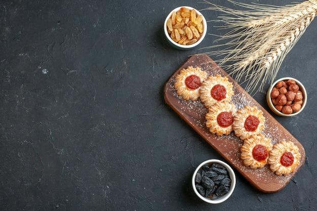 Bovenaanzicht koekjes met jam op houten bord noten in kleine kommen tarwe spikes op donkere achtergrond met vrije ruimte