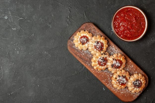 Bovenaanzicht koekjes met jam op houten plank jam in kom op donkere achtergrond met vrije ruimte