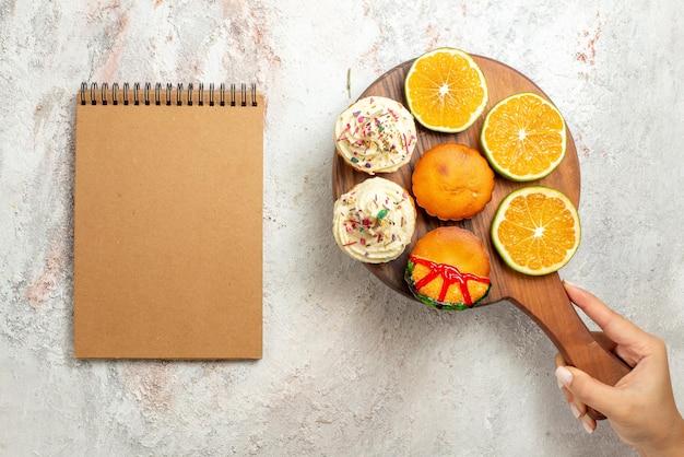 Bovenaanzicht koekjesbord met smakelijke koekjes en gesneden sinaasappel in de hand naast het crèmekleurige notitieboekje op tafel