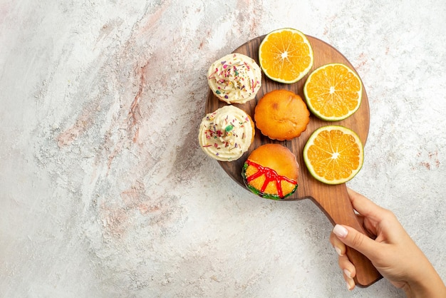 Bovenaanzicht koekjesbord met smakelijke koekjes en gesneden sinaasappel in de hand op tafel