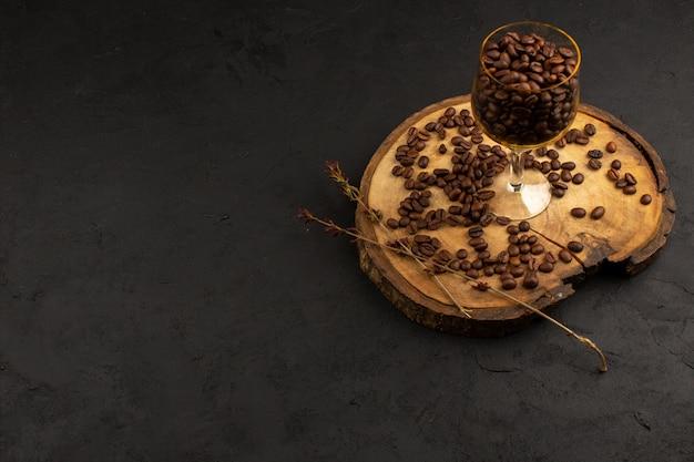 Bovenaanzicht koffie bruin zaden geheel binnen glas op het donker