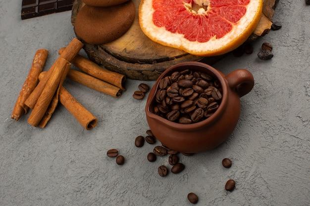 Bovenaanzicht koffie bruine zaden samen met kaneel en grapefruit op de grijze vloer