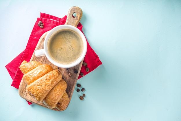 Bovenaanzicht koffie en croissant op tafel