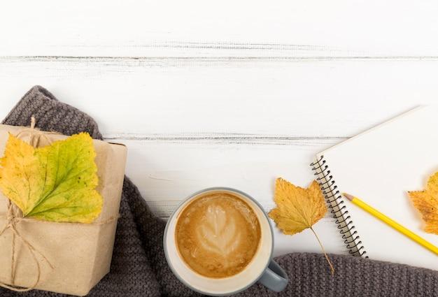 Bovenaanzicht koffie en herfst verlof op doos met kopie ruimte