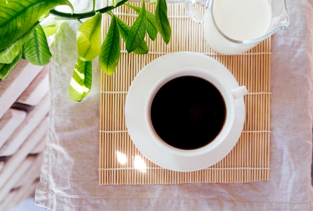 Bovenaanzicht koffie en melk op bamboe mat