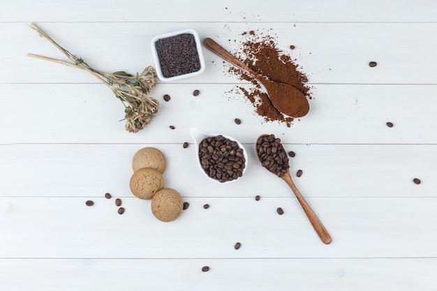 Bovenaanzicht koffie in beker met gemalen koffie, koffiebonen, gedroogde kruiden, koekjes op houten achtergrond. horizontaal