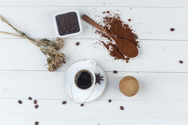 Bovenaanzicht koffie in beker met gemalen koffie, koffiebonen, gedroogde kruiden, specerijen