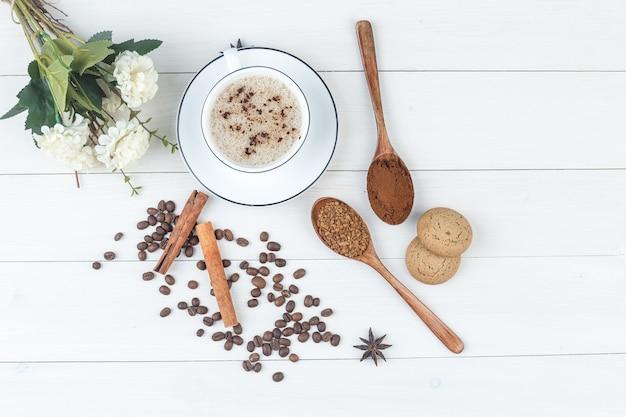 Bovenaanzicht koffie in beker met gemalen koffie, kruiden, koffiebonen, koekjes, bloemen op houten achtergrond. horizontaal