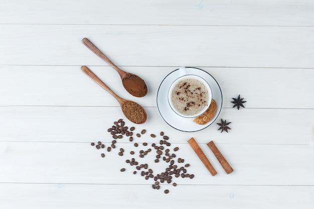 Bovenaanzicht koffie in beker met gemalen koffie, kruiden, koffiebonen, koekjes op houten achtergrond. horizontaal