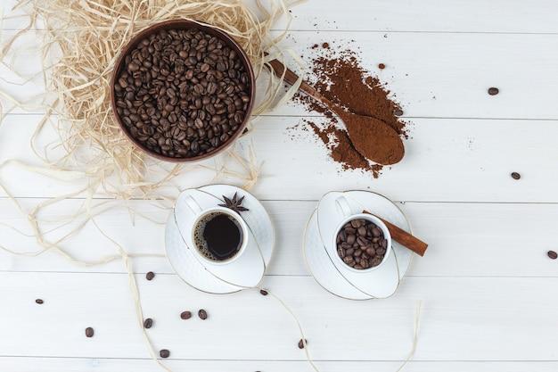 Bovenaanzicht koffie in beker met gemalen koffie, kruiden, koffiebonen op houten achtergrond. horizontaal