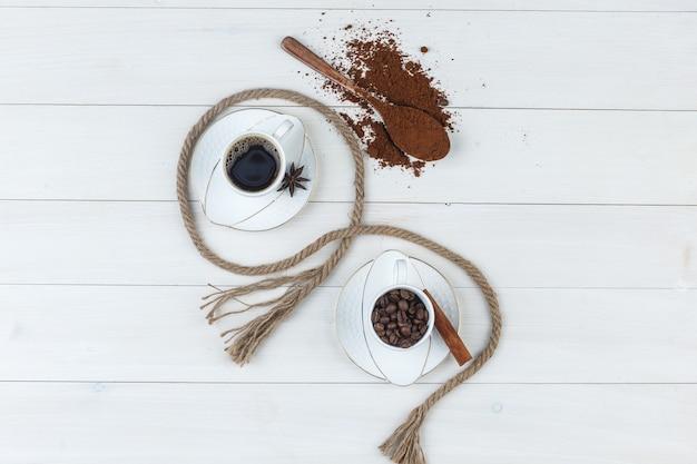 Bovenaanzicht koffie in beker met gemalen koffie, kruiden, koffiebonen, touw op houten achtergrond. horizontaal