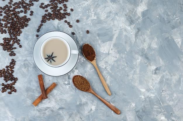 Bovenaanzicht koffie in beker met koekjes, koffiebonen, gemalen koffie, kaneelstokjes op grijze gips achtergrond. horizontaal