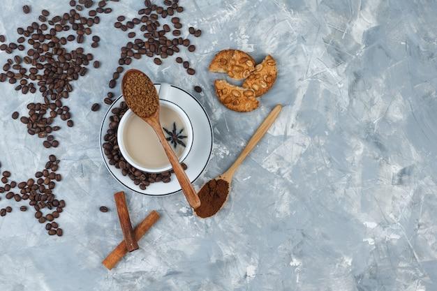 Bovenaanzicht koffie in beker met koekjes, koffiebonen, gemalen koffie, kruiden op grijze gips achtergrond. horizontaal