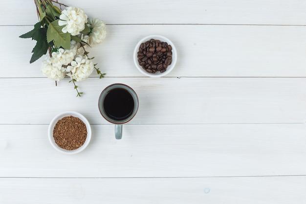 Bovenaanzicht koffie in beker met koffiebonen, bloemen, gemalen koffie op houten achtergrond. horizontaal