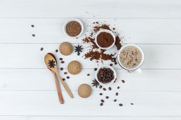 Bovenaanzicht koffie in beker met koffiebonen, gemalen koffie, kruiden, koekjes, houten lepels op houten achtergrond. horizontaal