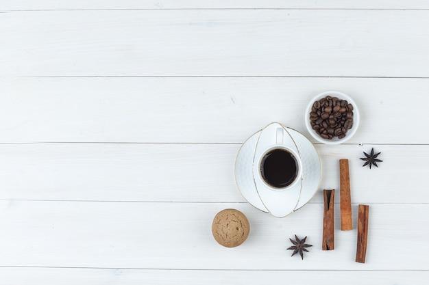 Bovenaanzicht koffie in beker met koffiebonen, kruiden, koekje op houten achtergrond. horizontaal