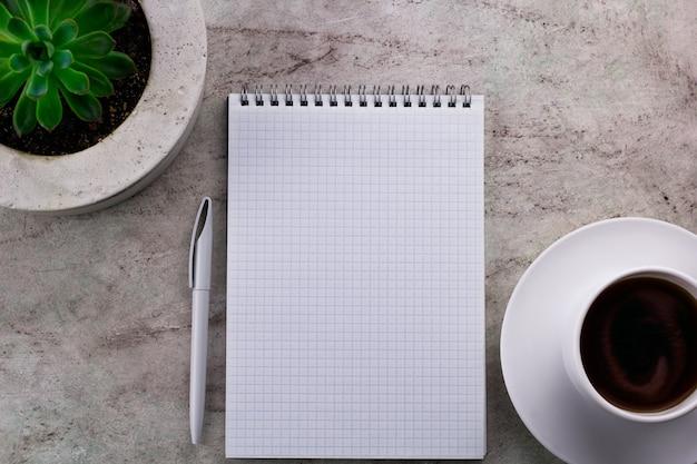 Bovenaanzicht koffie, open mock-up notebook en succulent