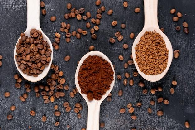 Bovenaanzicht koffiebonen en oploskoffie in houten lepels op een donkere ondergrond