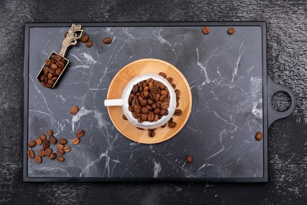 Bovenaanzicht koffiebonen in cup op de zwarte snijplank