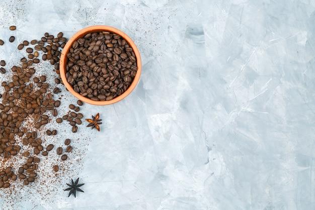 Bovenaanzicht koffiebonen in een kom met kruiden op grunge achtergrond