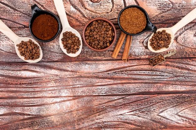 Bovenaanzicht koffiebonen in lepels en platen op houten oppervlak