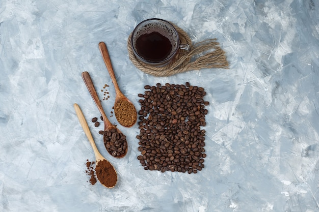Bovenaanzicht koffiebonen, kopje koffie met koffiebonen, oploskoffie, koffiemeel in houten lepels, touwen, koekjes op lichtblauwe marmeren achtergrond. horizontaal
