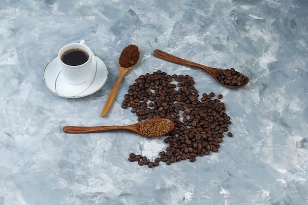 Bovenaanzicht koffiebonen, kopje koffie met oploskoffie, koffiemeel, koffiebonen in houten lepels op lichtblauwe marmeren achtergrond. horizontaal